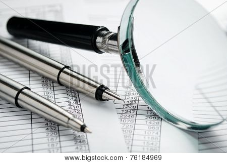 Magnifying Glass And Pens On Top Of Reports