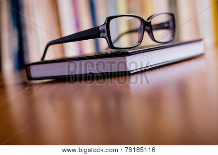 Eyeglasses On Top Of The Book At The Table