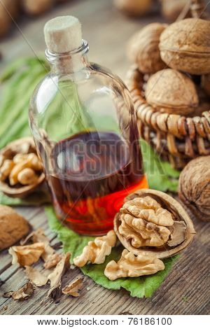 Walnuts, Bottle Of Tincture Or Oil And Wicker Basket With Nuts On Old Table.