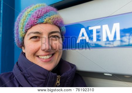 Smiling Young Woman Standing At An Atm