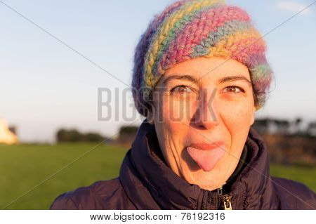 Smiling Young Woman Playfully Sticking Out Her Tongue