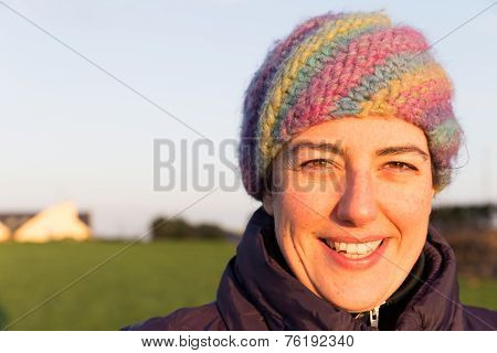 Smiling Young Woman Wearing A Woolen Hat Outside