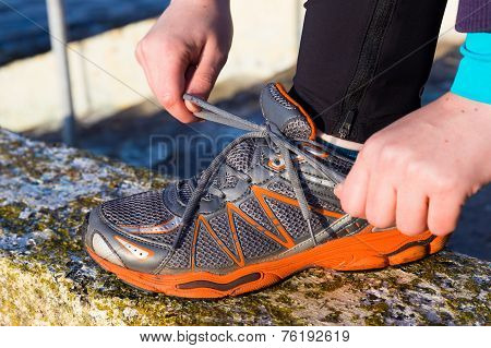 Female Tying The Shoe Laces On Her Running Shoes