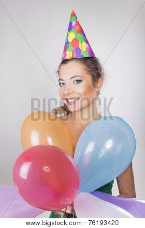 Brunette Woman in a Birthday Cap Holding Balloons and Smile Happily