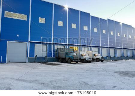 Modern Warehouse Outside,  Trucks Are Unloaded At Loading Docks, Evening.