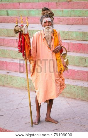 VARANASI, INDIA - MARCH, 21: An unidentified sadhu - Hindu holy man seeks alms in front of a ghat along the river Ganges on March 21, 2013 at Varanasi, Uttar Pradesh, India.