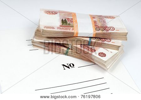 Horizontal picture of packs of the ruble notes piled on the white folder