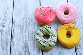 stock photo of donut  - Delicious donuts with glaze on colorful wooden background - JPG