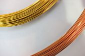 stock photo of bundle  - Sections of a bundle of brass wire and a bundle of copper wire - JPG