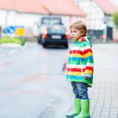 stock photo of rainy season  - Funny cute kid boy walking in city through rain wearing colorful rain coat and green boots outdoors at rainy day - JPG