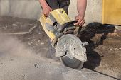 picture of sawing  - Asphalt or concrete cutting with saw blade at construction site - JPG