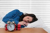 stock photo of time-bomb  - Beautiful young woman sleeping in bed with a time bomb alarm clock - JPG