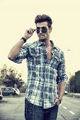pic of goatee  - Trendy cool young man standing outside smoking lowering sunglasses wearing shirt and jeans - JPG