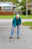 stock photo of hopscotch  - Senior woman playing hopscotch in the driveway - JPG
