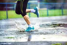 picture of rainy weather  - Young man running on asphalt sports field in rainy weather - JPG