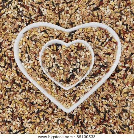 Healthy seven grain and cereal food mixture in heart shaped bowls and forming an abstract background.