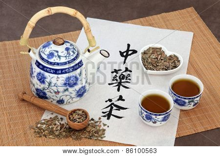 Ginkgo herb tea also used in chinese herbal medicine, with teapot, cup and calligraphy script on rice paper over bamboo. Translation reads as chinese herbal tea.