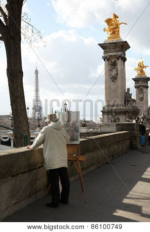 PARIS, FRANCE - MARCH 04, 2014:  Old man artist drawing the eiffel tower along the la seine river in Paris, France.