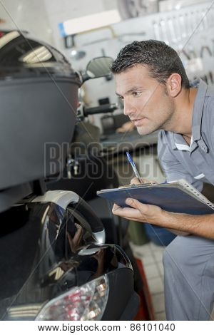 Mechanic assessing a broken scooter