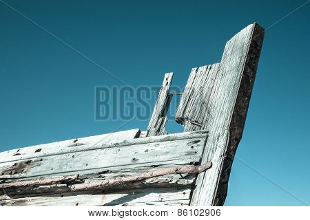Old wooden boat bow against blue sky