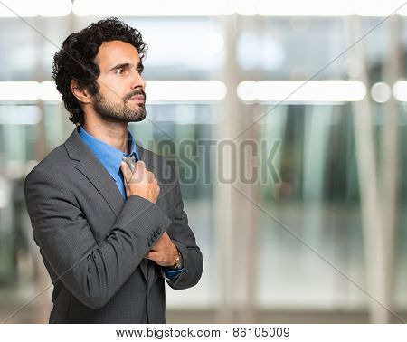 Businessman adjusting his necktie. Copy-space