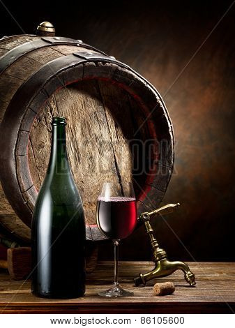 Still-life with glass of wine, bottle and barrel on the table in the cellar.