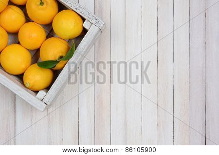 A crate of fresh picked lemons on a rustic white wood table in the upper left corner of the frame. Horizontal format with copy space.