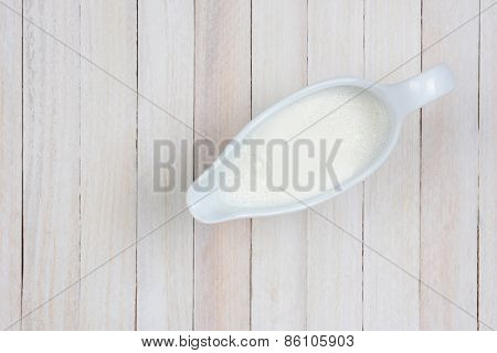 Overhead shot of a pitcher of milk on a rustic whitewashed kitchen table. Horizontal format with copy space.
