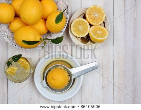 High angle shot of squeezing lemons still life shot from a high angle on a rustic white wood kitchen table.