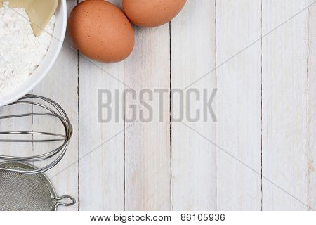 High angle shot of a baking still life, The objects, flour bowl, whisk, strainer and eggs are in the upper left corner, leaving plenty of copy space.