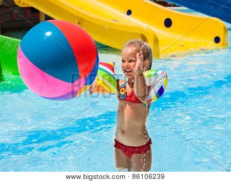 Child on water slide at aquapark. Girl playing beach ball. Summer holiday.