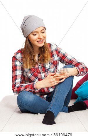 Teenage girl in a checked shirt with a smartphone