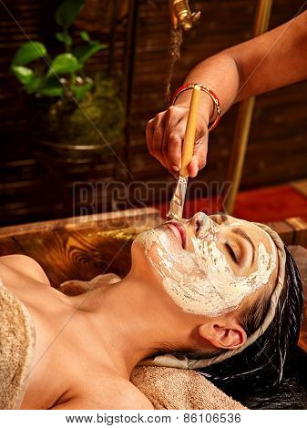 Woman having facial mask at ayurveda spa. India culture.