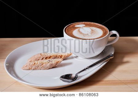 A nice view of capuccino and Italian pastries biscotti on black background