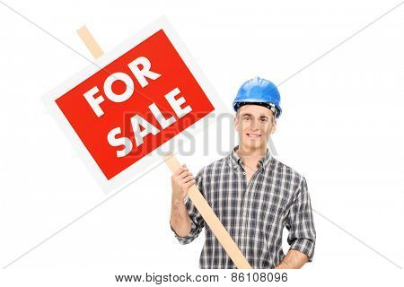 Young confident male engineer wearing blue helmet and holding a for sale sign isolated on white background