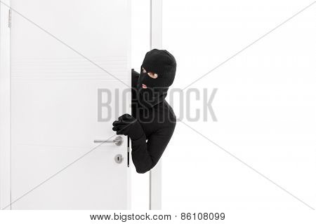 Studio shot of a stealthy thief breaking into a room through a door and carefully looking around isolated on white background