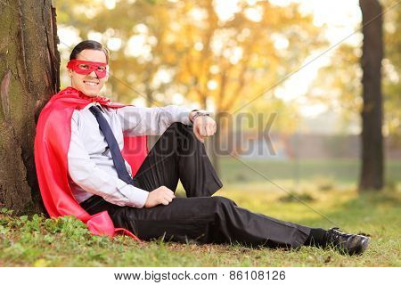 Joyful man in superhero outfit sitting on a grass, leaned on a tree. The shot is in a park during early autumn
