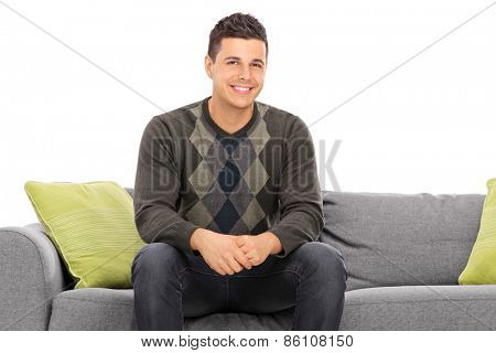 Cheerful handsome young man sitting on a modern grey sofa with green pillows isolated on white background