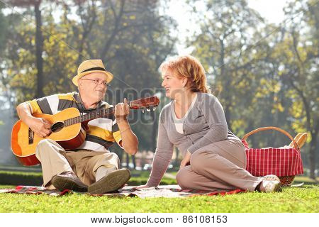 Senior man playing guitar to his wife on a picnic, seated on a blanket. The shot is in a city park during early autumn
