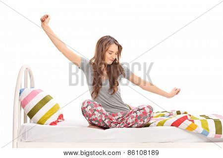 Beautiful woman waking up in the morning and stretching seated on a bed isolated on white background