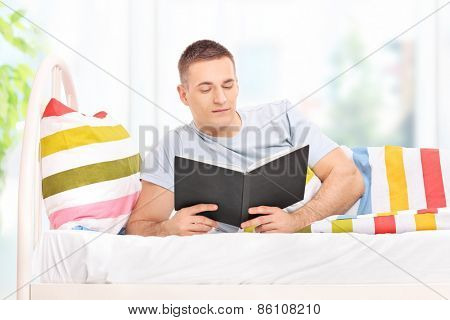 Relaxed young man reading a book and lying in bed at home covered with a striped blanket
