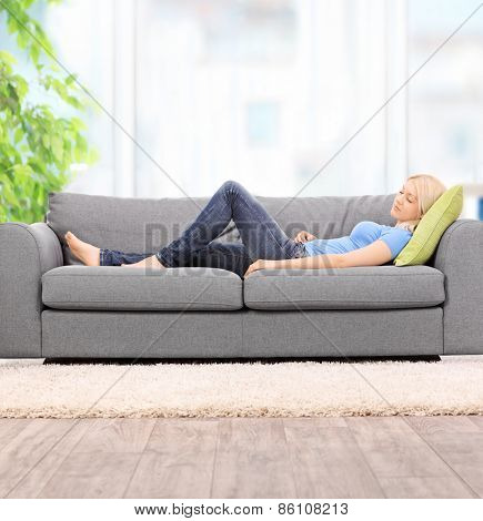 Young blond woman sleeping on a modern gray sofa at home shot with tilt and shift lens