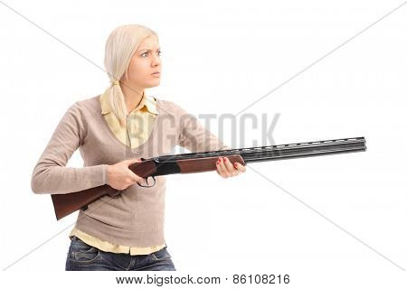 Furious young blond woman holding a shotgun ready to shoot isolated on white background