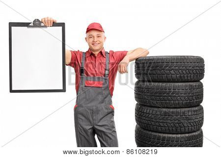 Studio shot of a male mechanic holding a clipboard with a blank paper on it and leaning on a stack of tires isolated on white background
