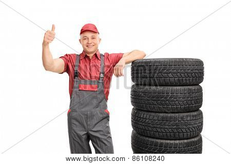 Young repairman in a jumpsuit giving a thumb up and leaning on a stack of tires isolated on white background