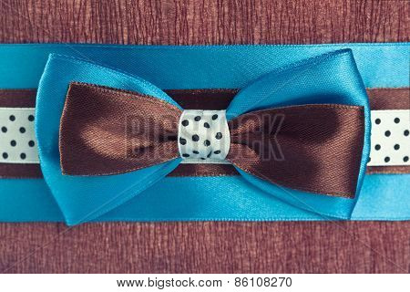 Blue, Brown And White Polka Dot Ribbons With Bow On Brown Paper