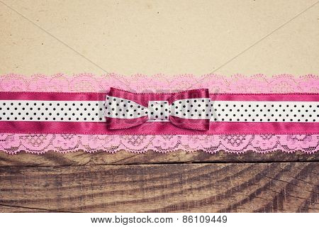 Vintage Background With Wood, Old Paper And Pink And White Polka Dot Ribbon With Bow