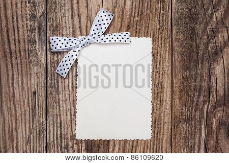 Blank Paper Sheet With White Polka Dot Bow On Wooden Background