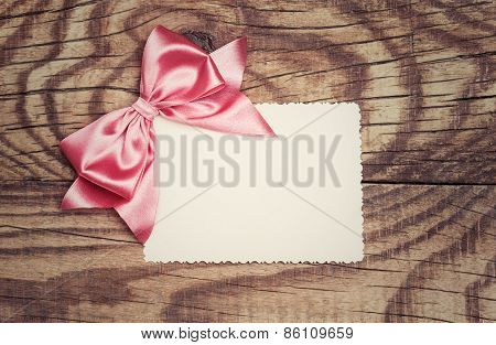 Blank Paper Sheet With Pink Bow On Wooden Background