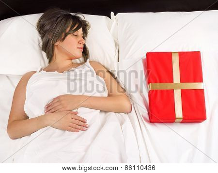 Woman In Bed With Present